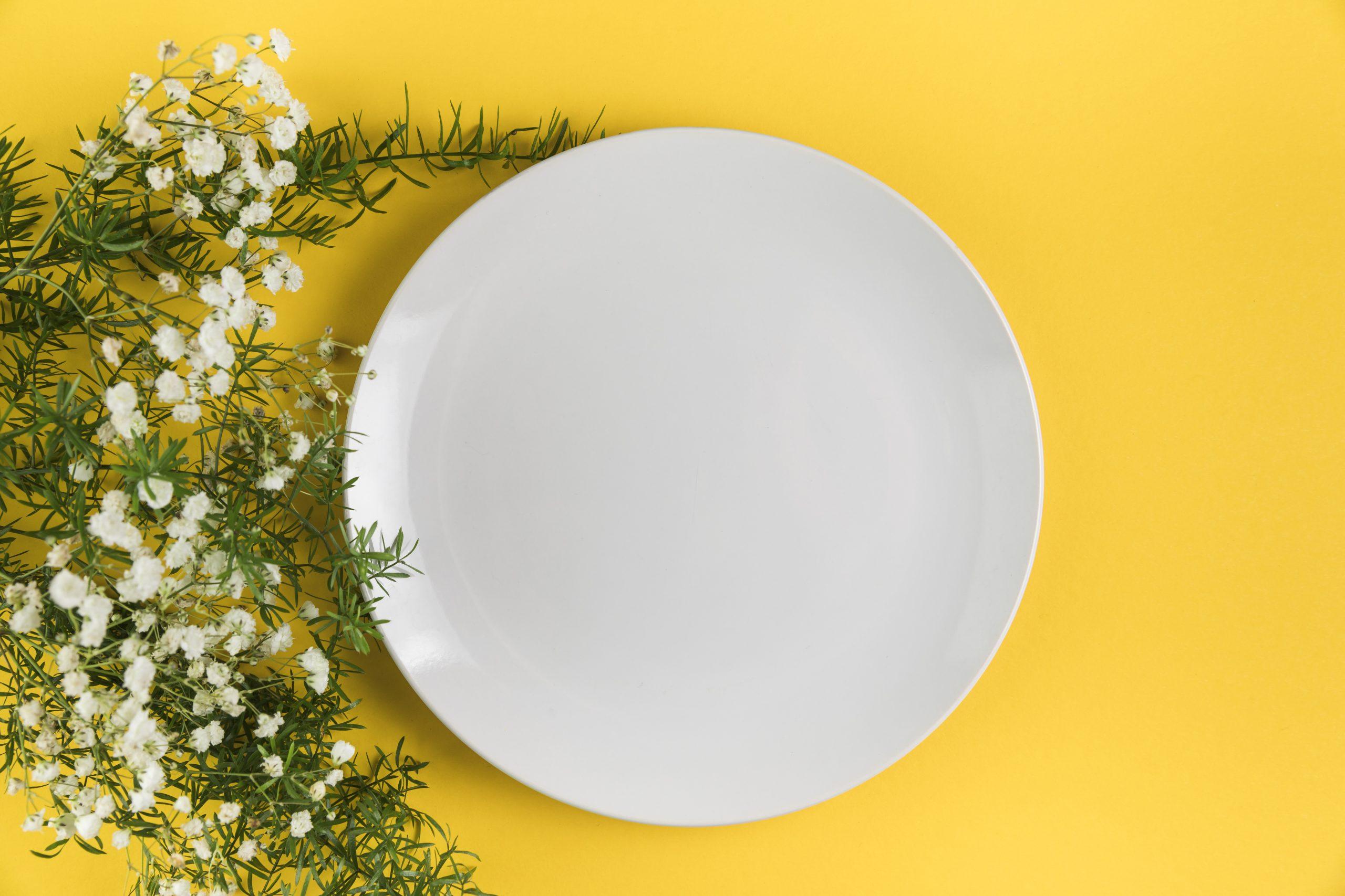 white-empty-plate-near-gypsophila-flowers-yellow-background